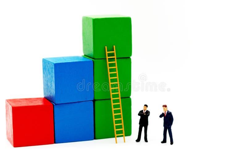 Povos diminutos: Homens de negócios com gráfico do crescimento e escada da madeira, foto de stock royalty free