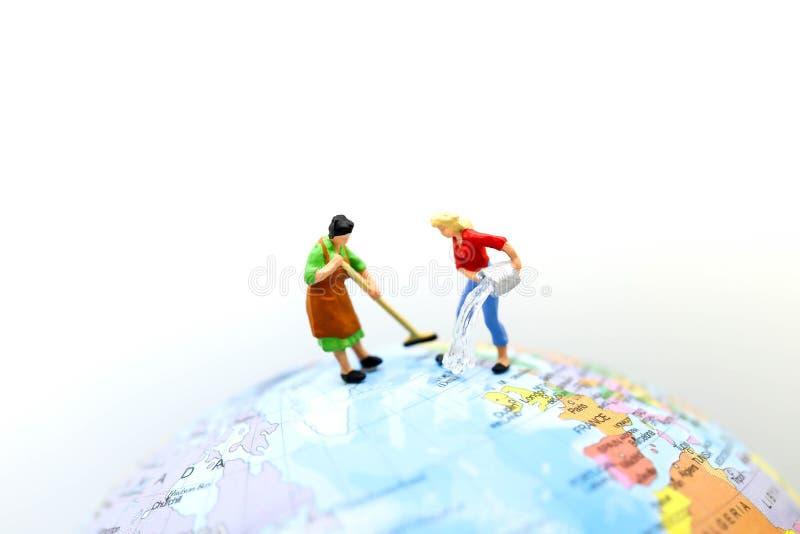 Povos diminutos: Limpeza da empregada doméstica ou da dona de casa no mini mapa do mundo imagens de stock royalty free