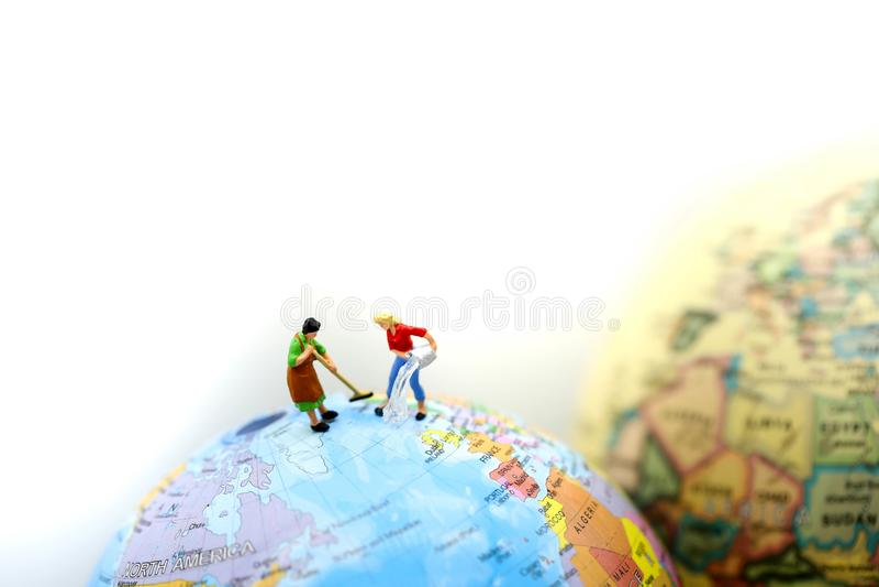 Povos diminutos: Limpeza da empregada doméstica ou da dona de casa no mini mapa do mundo fotografia de stock royalty free