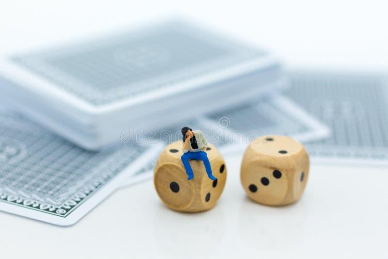 Povos diminutos: O homem que senta-se em dados e em plataforma de cartão Uso da imagem para o jogo, conceito do negócio imagem de stock