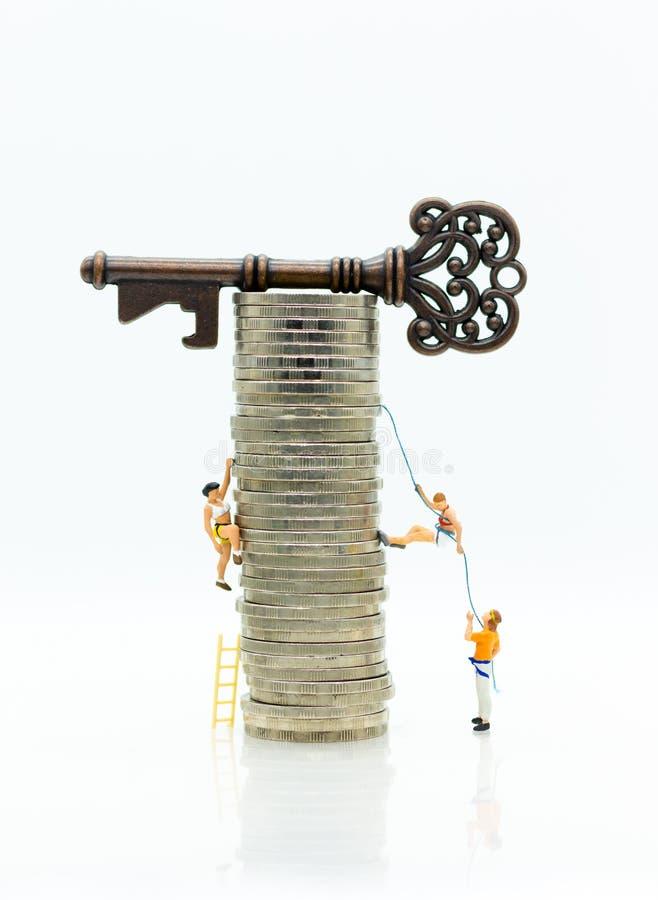 Povos diminutos: Os montanhistas estão escalando moedas para obter às chaves mestras Uso da imagem para mover-se para a frente pa foto de stock
