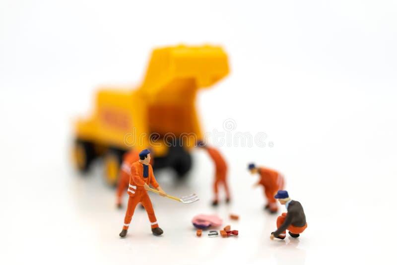 Povos diminutos: Os trabalhadores estão limpando, área para obras Imagens do uso para a ind?stria da constru??o imagens de stock royalty free