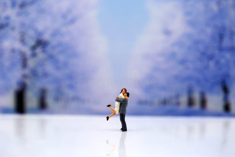 Povos diminutos: Pares de amor com fundo do inverno da neve, Lo imagem de stock
