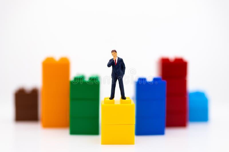 Povos diminutos: Parte dianteira do suporte do homem de negócios do painel, gráficos da exposição, margens de benefício do fundo  foto de stock