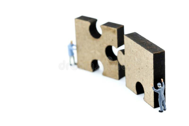 Povos diminutos: partes do enigma de serra de vaivém do impulso do trabalhador, negócio v fotografia de stock