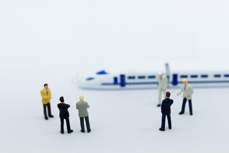 Povos diminutos: Planeamento do homem de negócios em um projeto para um trem para viajar Uso da imagem para o transporte, conceit foto de stock royalty free