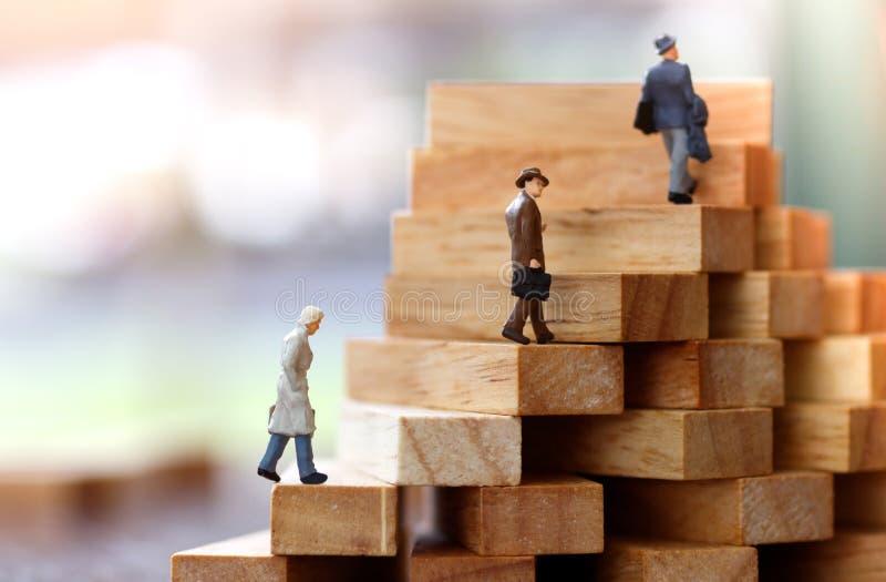 Povos diminutos que andam na etapa da pilha do bloco de madeira crescimento no conceito do negócio imagem de stock