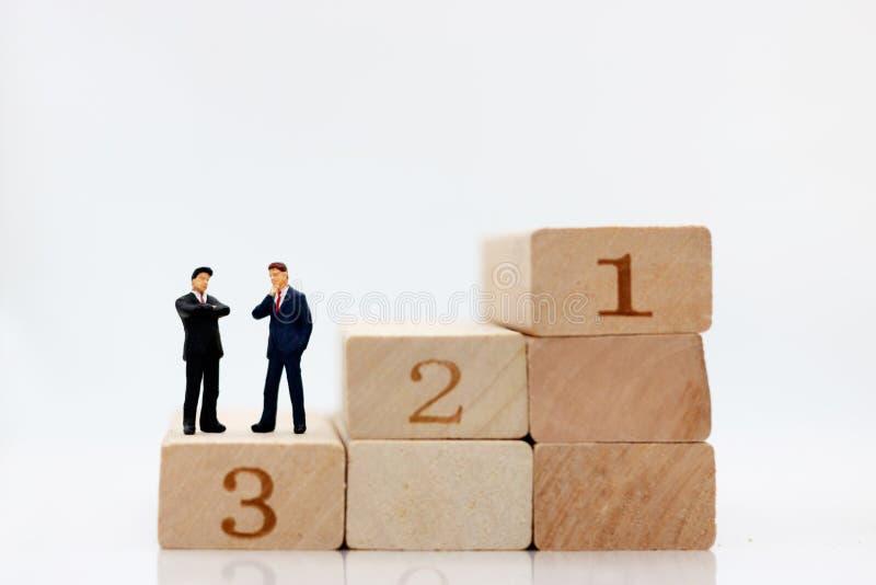 Povos diminutos que estão na etapa da pilha do bloco de madeira imagens de stock