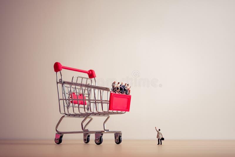 Povos diminutos que sentam-se em um carrinho de compras gigante Salvamento e sh fotografia de stock royalty free