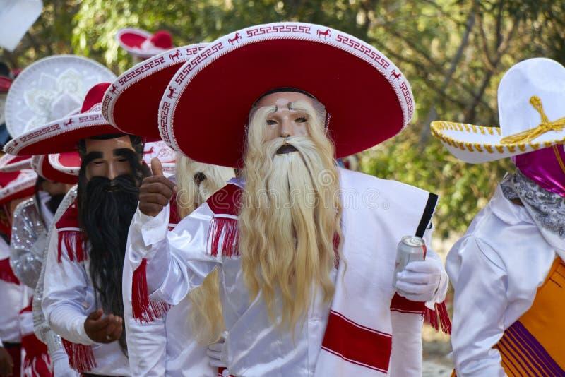 Povos disfarçados como um charro ou um mariachi mexicano com um terno branco e máscaras imagens de stock royalty free