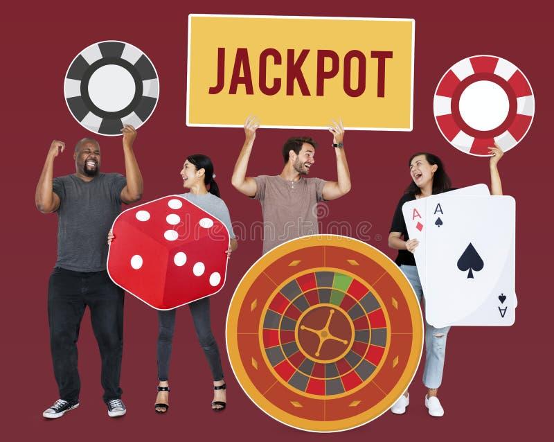 Povos diversos felizes que guardam ícones do casino imagem de stock royalty free