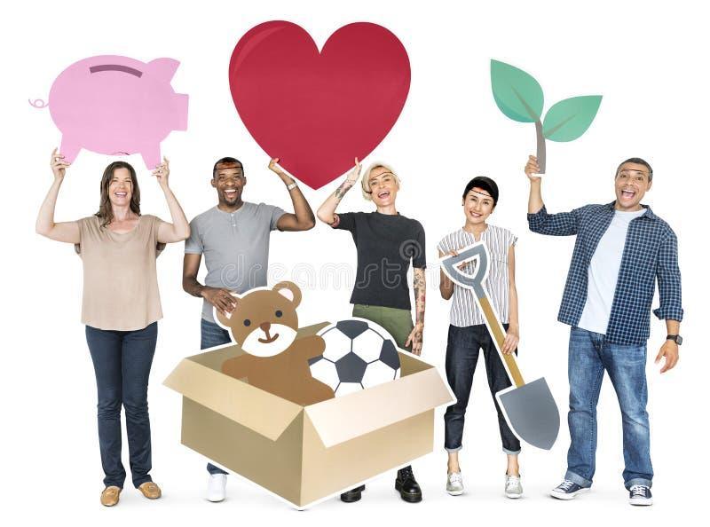 Povos diversos felizes que guardam símbolos da caridade fotos de stock