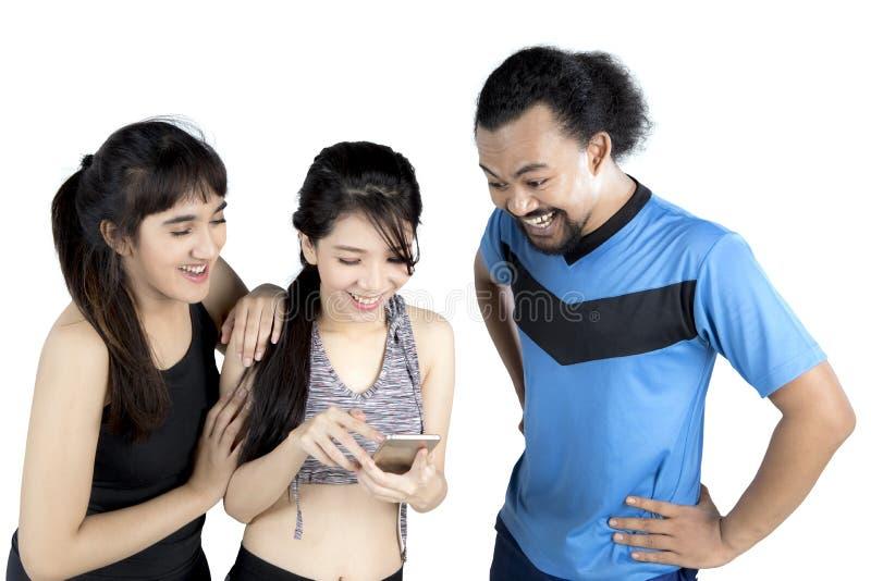 Povos diversos que exercitam junto com um smartphone foto de stock royalty free