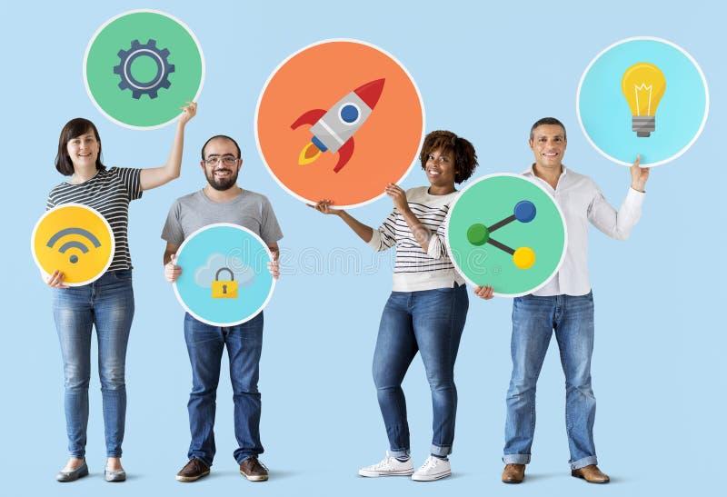 Povos diversos que guardam ícones da tecnologia imagem de stock