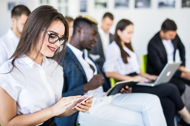 Povos diversos que trabalham em telefones celulares, empregados incorporados do escritório que guardam smartphones no encontro Mu imagem de stock
