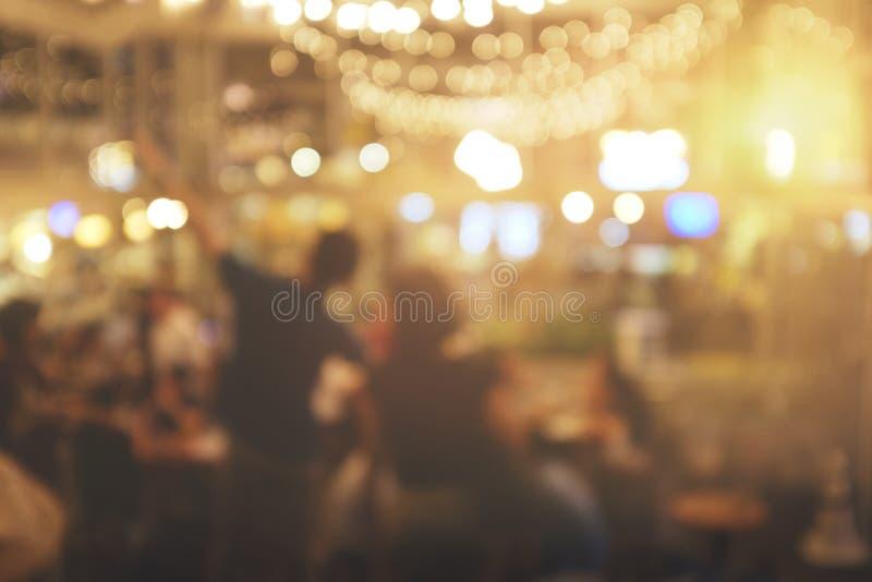 Povos do borrão no restaurante bokeh abstrato no partido da noite para o fundo imagens de stock