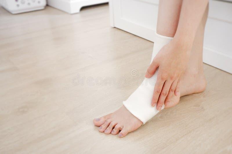 Povos do close up de um pé com Gauze Elastic Bandage branco Mãos nos pés e nos pés feridos na área da dor Tornozelo asiático da j foto de stock