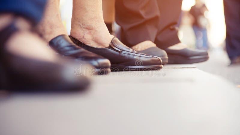 Povos do grupo as sapatas velhas envelhecidas mais velhas dos pés da pessoa e da mulher imagem de stock