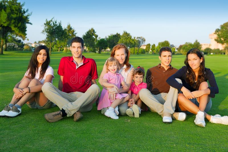 Povos do grupo dos amigos da família que sentam a grama verde fotos de stock royalty free