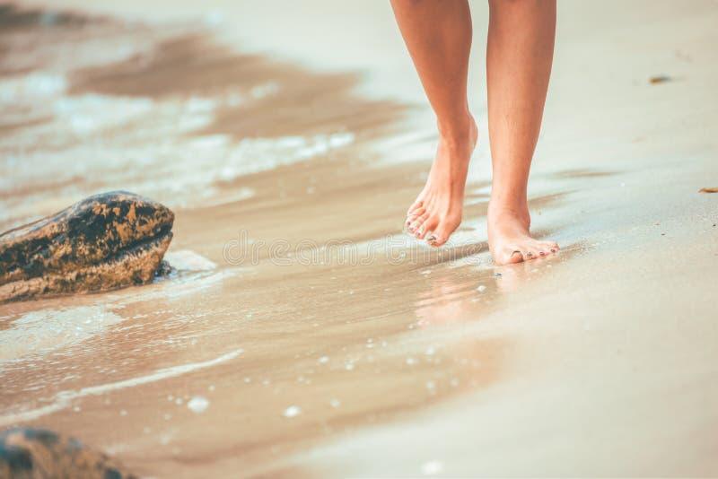 Povos do pé que andam na praia e no volume de água imagens de stock