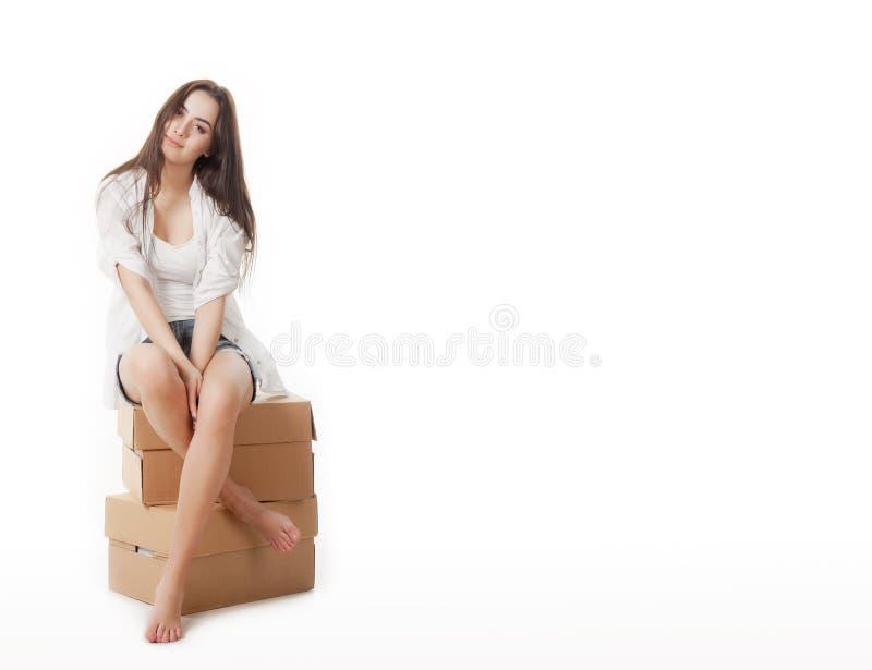 Povos do sinal Mulher que senta-se em caixas de cartão vazias Modelo louro bonito novo ocasional isolado no fundo branco imagem de stock royalty free