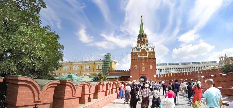 Povos do turista que andam perto das torres da trindade e do Kutafya do Kremlin de Moscou imagens de stock royalty free