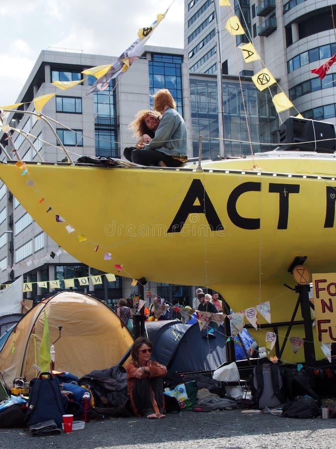 Povos e barracas no protesto da rebelião da extinção com o barco na estrada que obstrui a ponte de victoria em leeds imagens de stock
