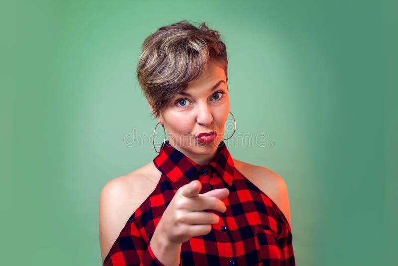 Povos e emoções - mulher nova feliz da forma que levanta para a câmera ao apontar em você imagens de stock
