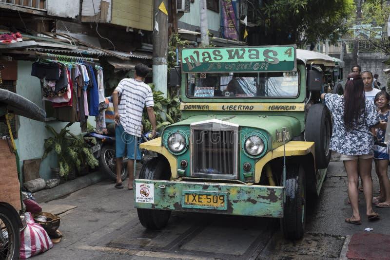 Povos e um jeepney parado em uma rua pequena de Manila fotografia de stock royalty free