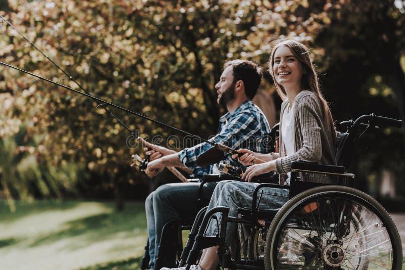 Povos em cadeiras de rodas com a vara de pesca no parque foto de stock