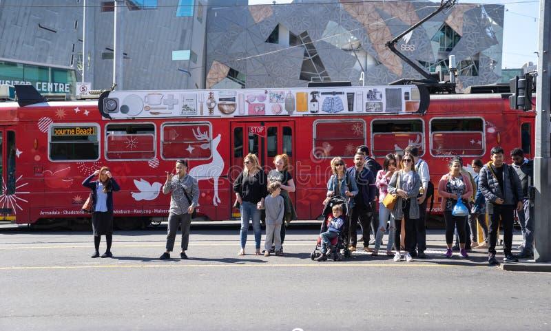 Povos em Melbourne que espera para cruzar a rua na frente de Federat imagem de stock
