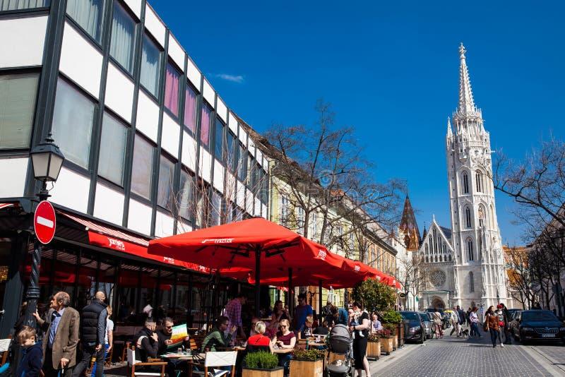 Povos em restaurantes ao lado de Matthias Church nas ruas bonitas do coração de Buda Castle District imagens de stock royalty free