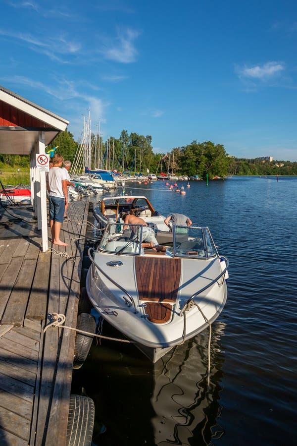 Povos em um barco a motor amarrado em uma estação do reabastecimento do barco com veleiros foto de stock royalty free