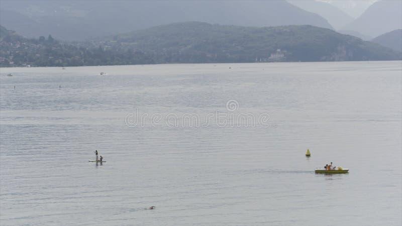Povos em um barco que flutua no lago em uma manhã nevoenta na frente das montanhas bonitas em Bangladesh a??o fotos de stock royalty free