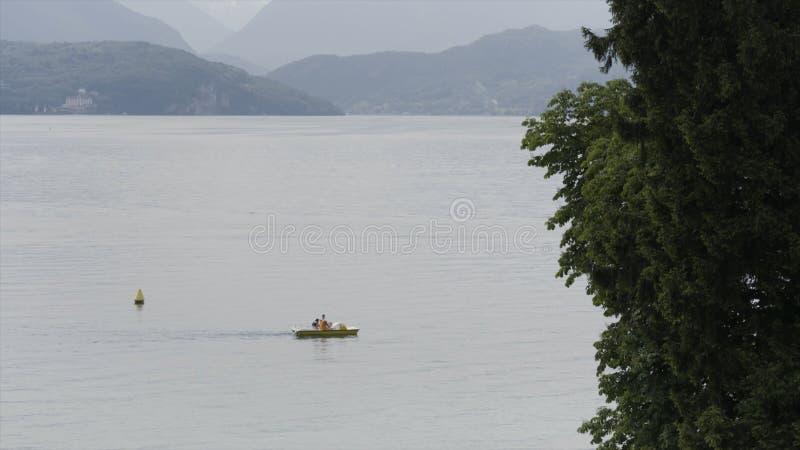 Povos em um barco que flutua no lago em uma manhã nevoenta na frente das montanhas bonitas em Bangladesh a??o imagens de stock royalty free