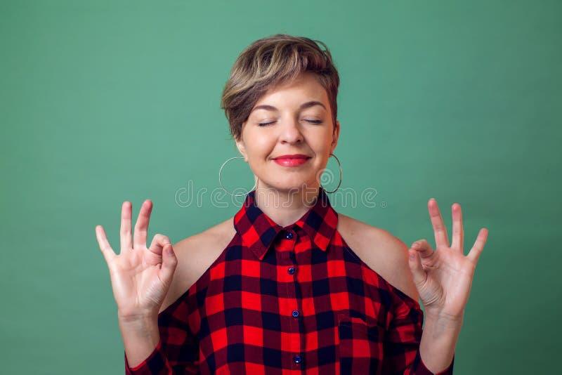 Povos, emoções e conceito da ioga - um retrato da mulher que relaxa e que sorri com os olhos fechados fazendo o gesto da meditaçã fotos de stock