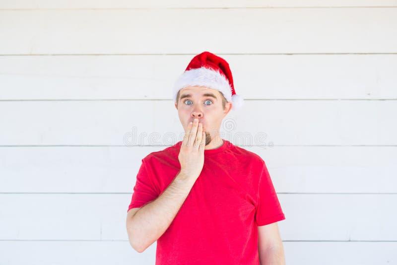 Povos, emoções e conceito do Natal - os jovens surpreenderam o homem no traje de Papai Noel no fundo branco foto de stock royalty free