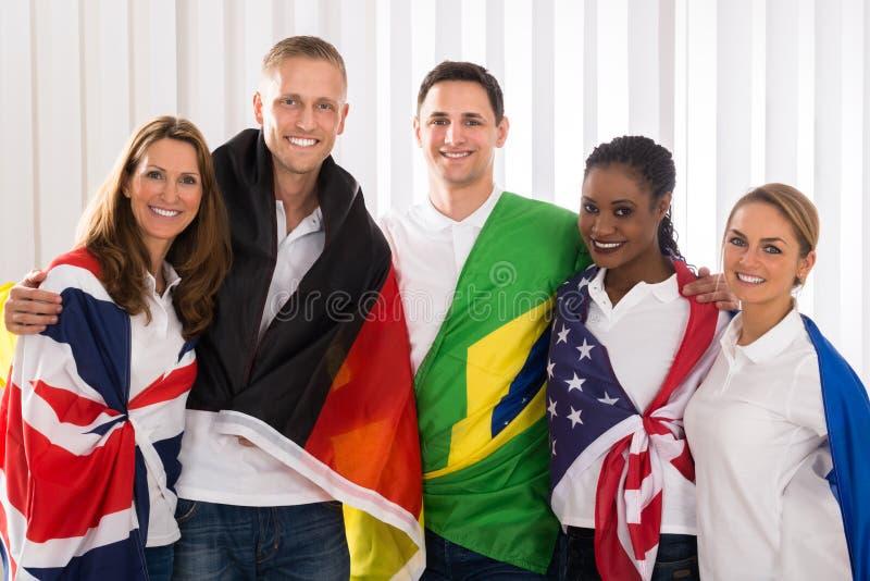 Povos felizes com as bandeiras dos países diferentes foto de stock royalty free
