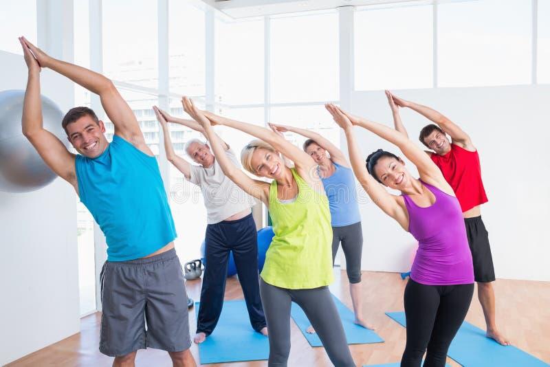 Povos felizes que fazem esticando o exercício na classe da ioga imagens de stock