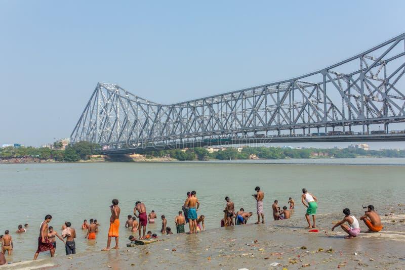 Povos indianos não identificados que tomam o banho no rio de Hooghly com uma ponte de Howrah no fundo em Calcutá, Bengal ocidenta fotografia de stock royalty free