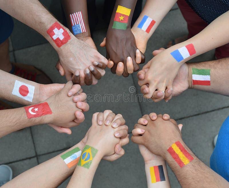 Povos internacionais com as bandeiras que guardam as mãos imagens de stock
