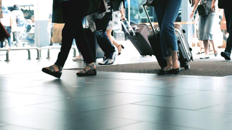 Povos irreconhecíveis com bagagens que andam no aeroporto terminal Feche acima deles os pés imagens de stock