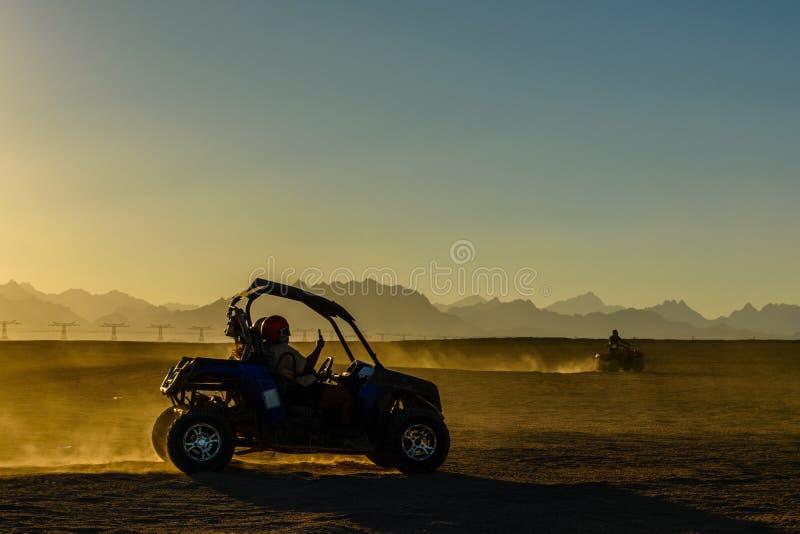 Povos irreconhecíveis que conduzem o carrinho durante a viagem do safari no por do sol no deserto árabe não longe da cidade de Hu imagens de stock