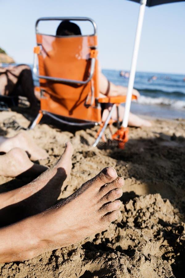 Povos irreconhecíveis que relaxam na praia fotografia de stock royalty free