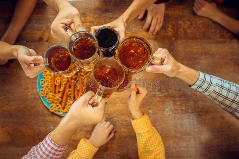 Povos, lazer, amizade e conceito de uma comunicação - amigos felizes que bebem vidros da cerveja, da fala e do tinido na barra fotos de stock royalty free