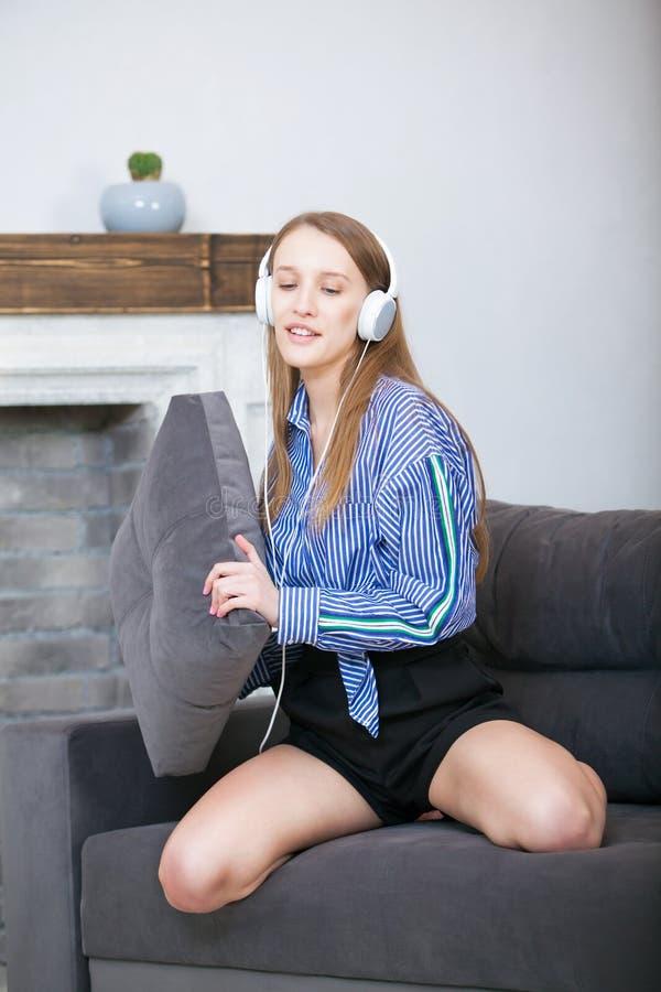 Povos, lazer e conceito da tecnologia - mulher ou adolescente feliz nos fones de ouvido que escutam a música do smartphone imagem de stock