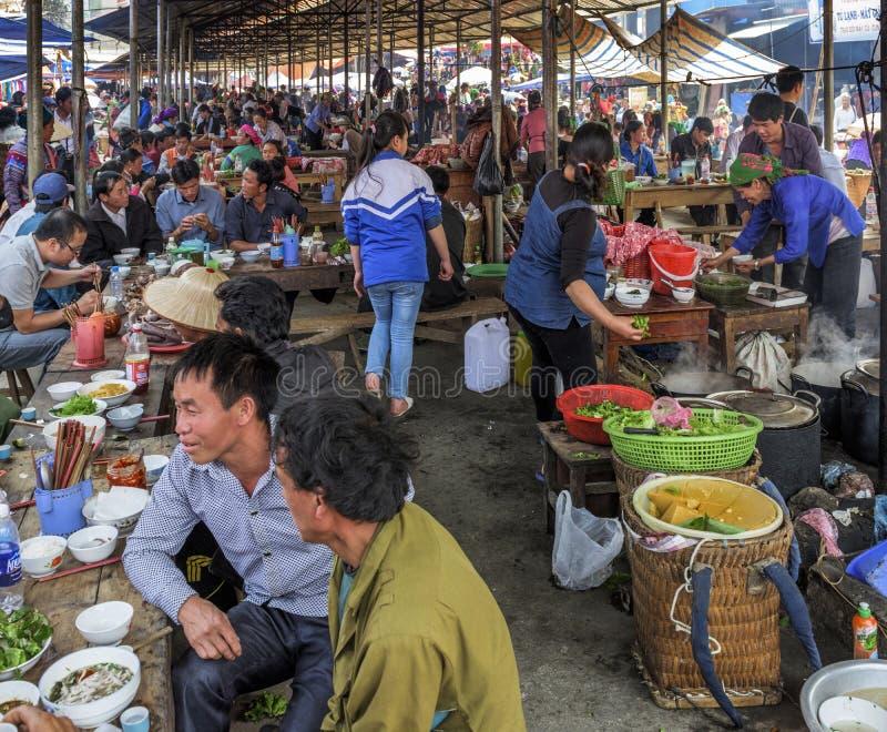 Povos locais da vila que comem e que têm um bate-papo em um mercado local em Sapa, Vietname fotos de stock royalty free