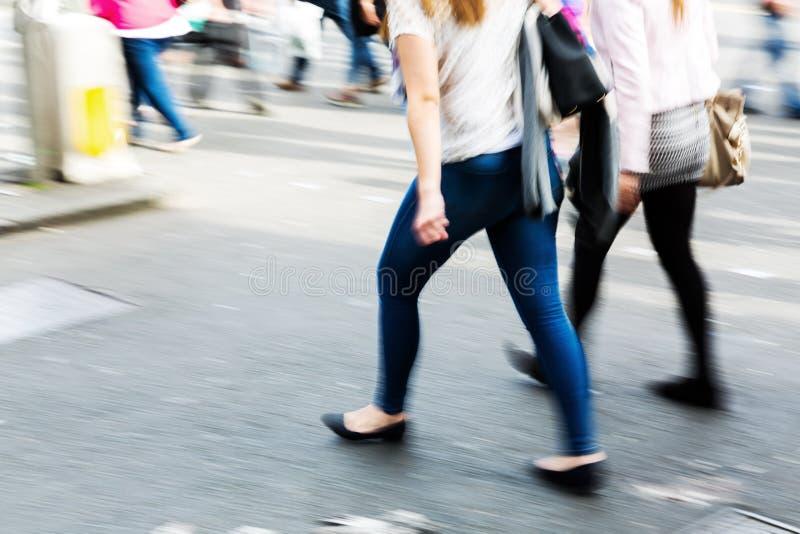 Povos mostrados no borrão de movimento que cruza uma rua fotos de stock royalty free