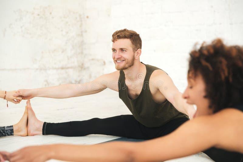 Povos multi-étnicos felizes no esticão do estúdio da ioga fotos de stock
