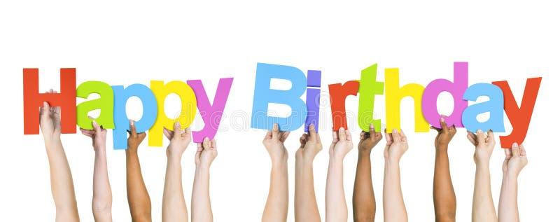 Povos multi-étnicos que guardam o feliz aniversario da palavra imagem de stock royalty free